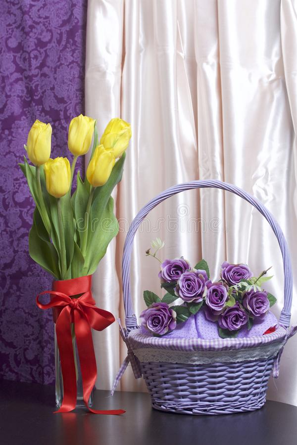 A bouquet of yellow tulips stands in a glass vase wrapped in a red ribbon tied to a bow. Next a wicker basket with flowers. stock photography