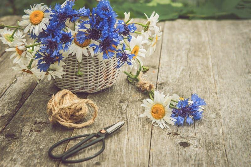 Bouquets de belles fleurs sauvages des marguerites et des bleuets sur un vieux fond en bois photos libres de droits