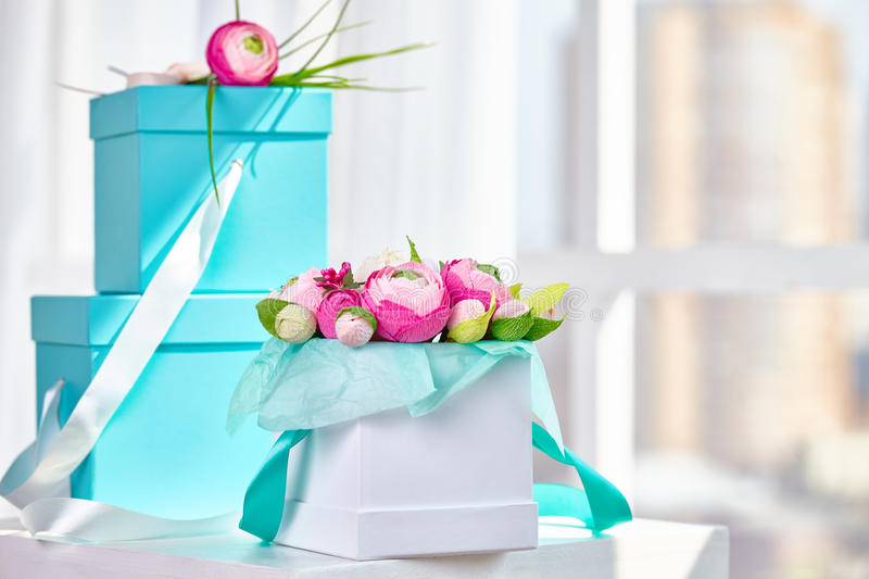 Bouquets of paper flowers in a cardboard square boxes stock photos