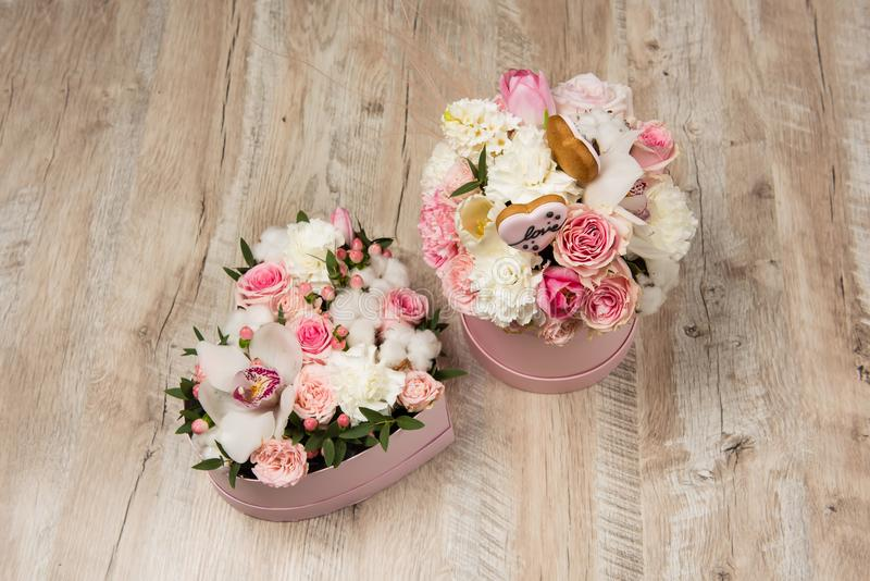 Two pink boxes with flowers indoors stock images
