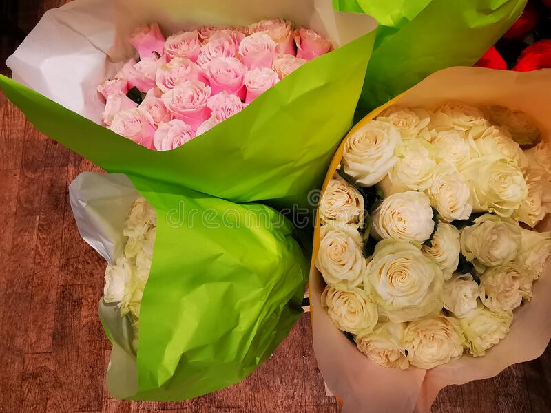 Bouquets of roses packaged with green paper stock photos