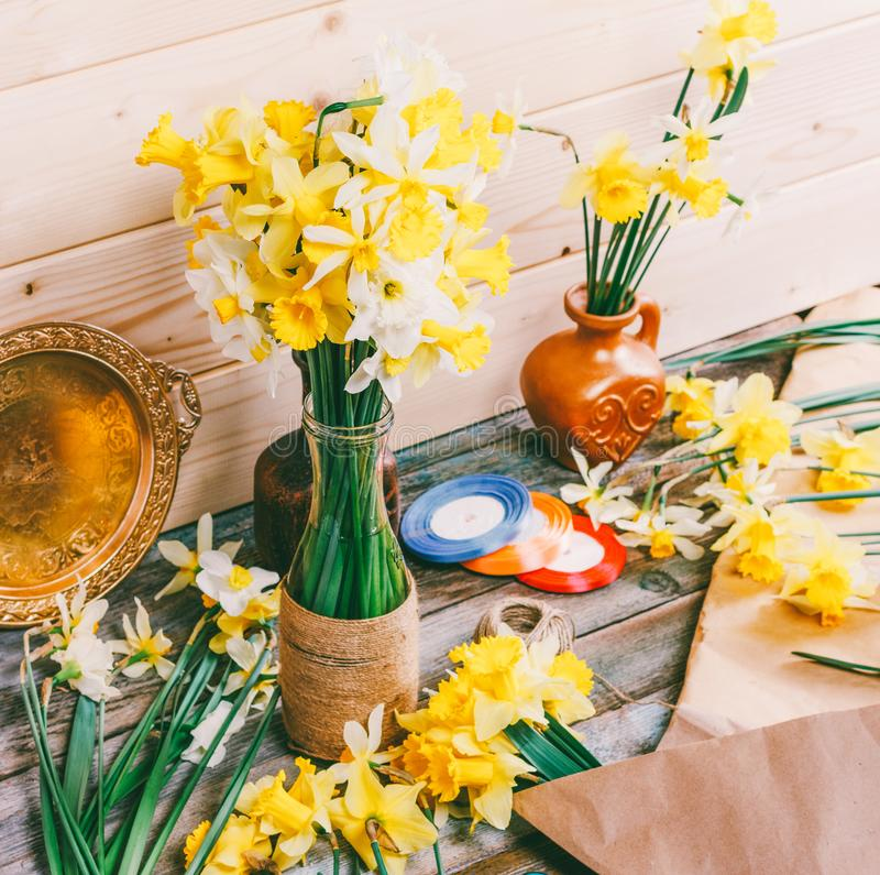 Bouquets of yellow daffodils flowers in a vase and a pitcher of Kraft paper and colored ribbons with a Hank of rope on a wooden ta royalty free stock photography