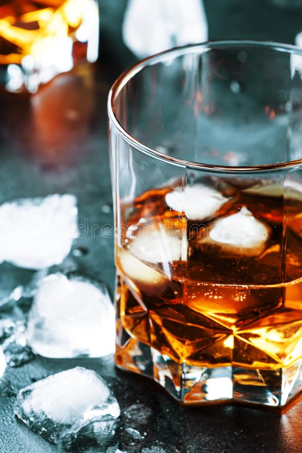 Bourbon with ice in glass on gray bar counter, selective focus stock photography