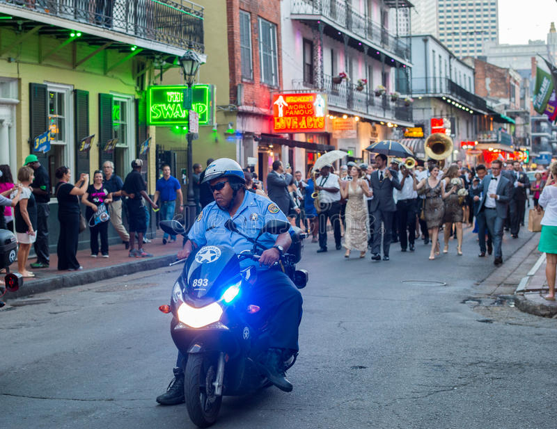 Bourbon Street, New Orleans. New Orleans, LA, USA - October 9, 2014: Police escort an early evening parade on Bourbon Street in New Orleans. Bourbon Street is royalty free stock photo