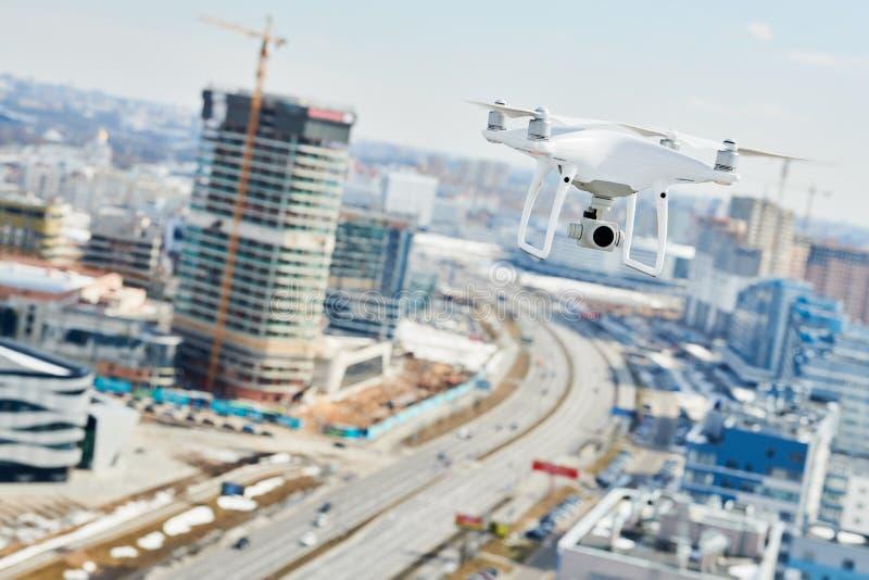 Bourdon avec l'appareil photo numérique planant au-dessus de la ville photo libre de droits