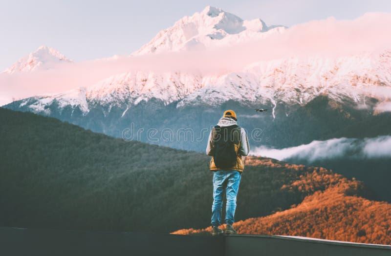 Bourdon de pilotage d'homme dans le mode de vie de voyage d'aventure de blogger de montagnes de coucher du soleil photo stock