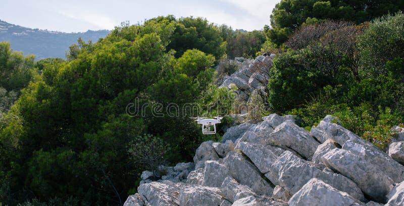 Bourdon, flyingon les roches blanches contre le contrôleur de rc de caméra de mouche de fpv de quadrocopter de ciel bleu image stock