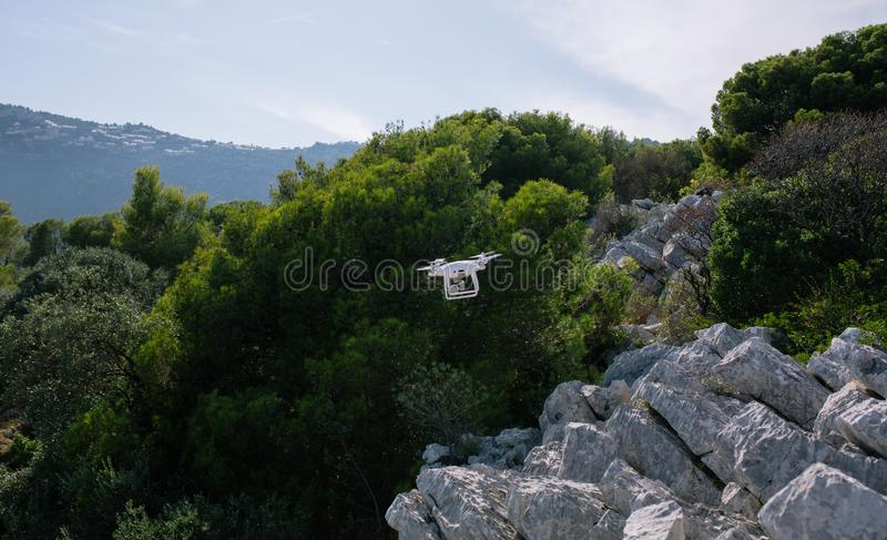 Bourdon, flyingon les roches blanches contre le contrôleur de rc de caméra de mouche de fpv de quadrocopter de ciel bleu photos libres de droits