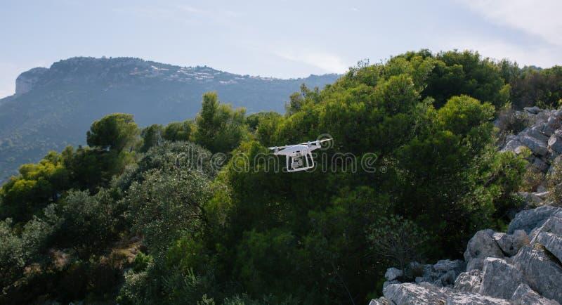 Bourdon, flyingon les roches blanches contre le contrôleur de rc de caméra de mouche de fpv de quadrocopter de ciel bleu photo stock