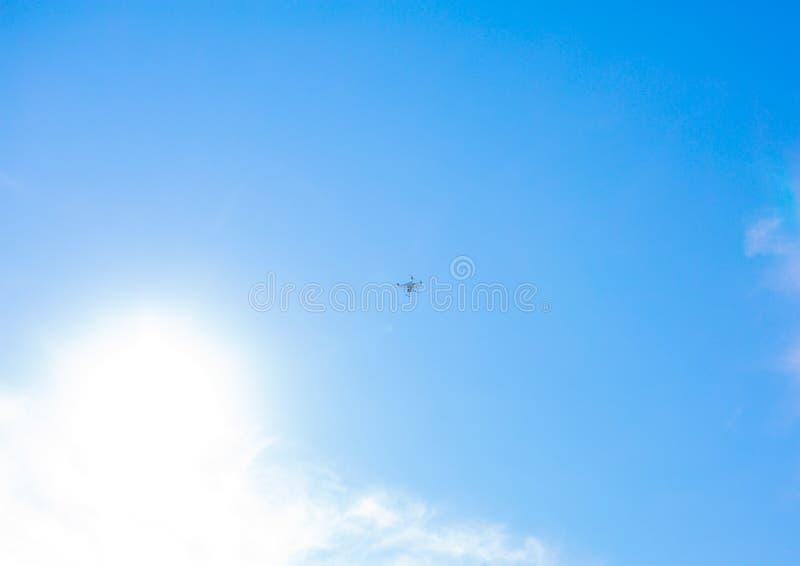 Bourdon, volant contre le contrôleur de rc de caméra de mouche de fpv de quadrocopter de ciel bleu photographie stock libre de droits