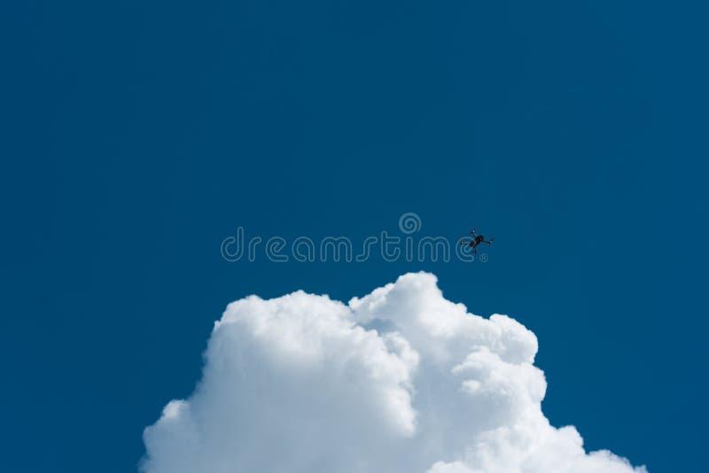 Bourdon volant haut avec le ciel nuageux bleu photo stock