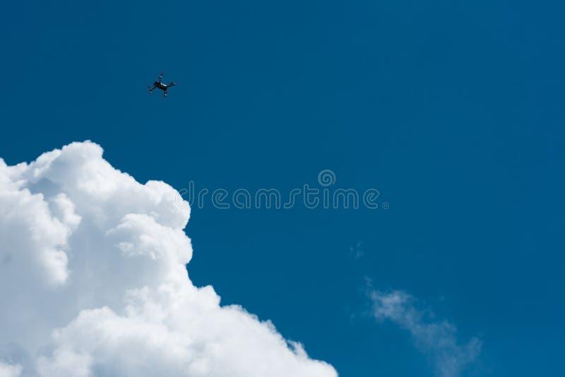 Bourdon volant haut avec le ciel nuageux bleu images stock
