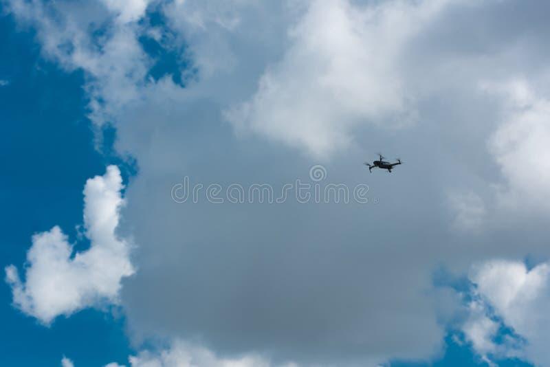 Bourdon volant haut avec le ciel nuageux bleu photographie stock