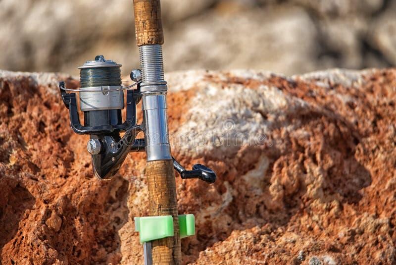 Bourdonné dans la photo, l'andle de canne à pêche et la bobine contre la roche photo libre de droits