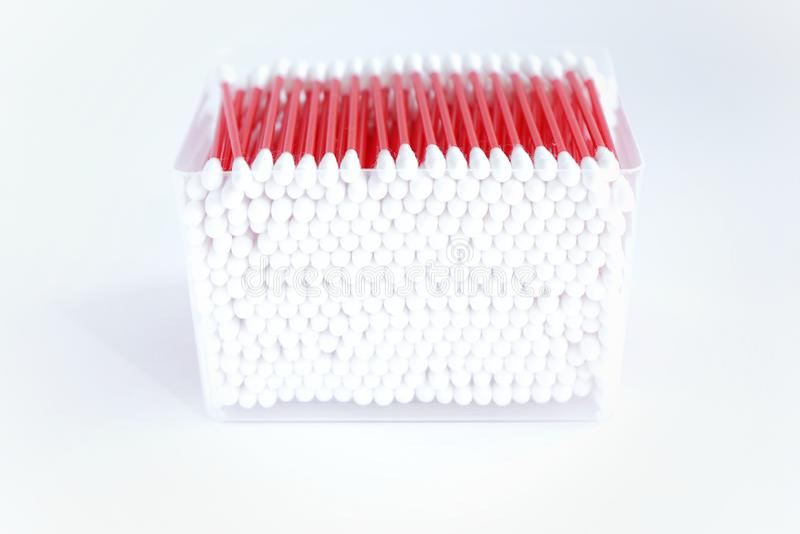 bourgeons de coton pour des oreilles avec un bâton lumineux rouge, dans une boîte, sur un fond blanc photo stock