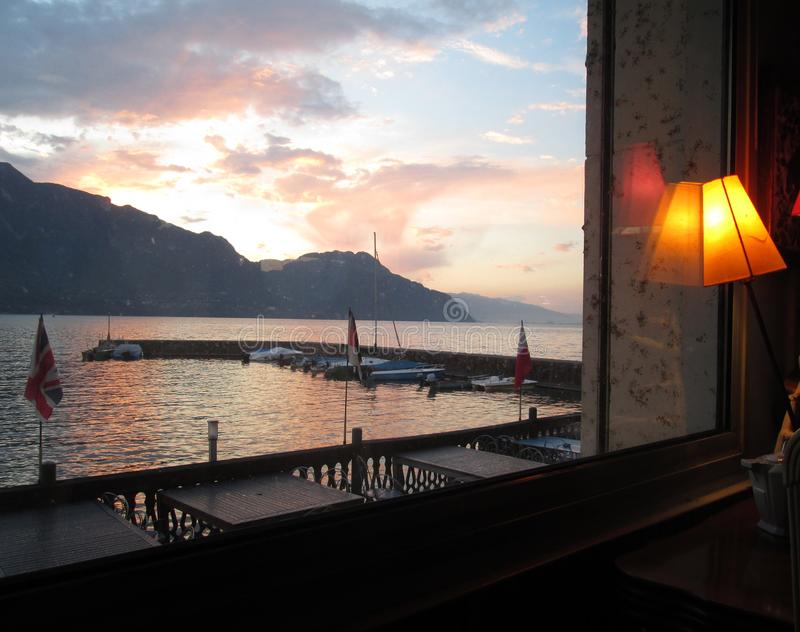 Bourget lake sunset, from restaurant terrace. Bourget lake sunset, from restaurant interior and terrace, Savoy, France stock photography
