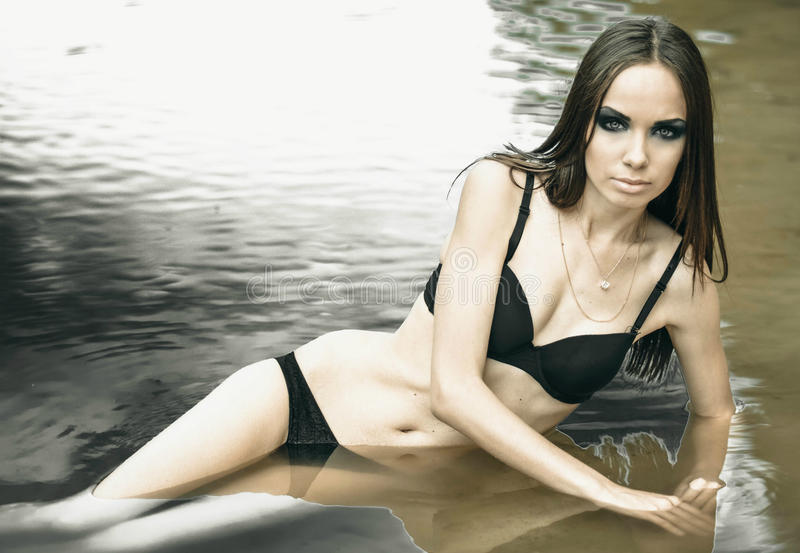 Sexual,seductive and beautiful,attractive girl in black bra and panties,swimsuit with long straight hair lay in water outdoors. stock photography