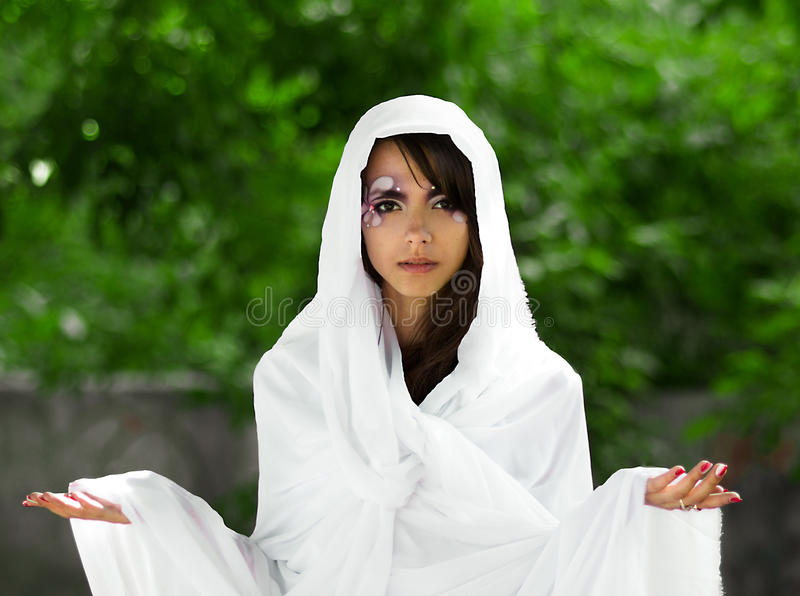 Portrait of serious,self-assured,powerful,confident girl in white dress royalty free stock image