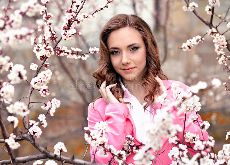 Attractive,pretty,awesome,nice girl stand in blossoming garden with white,rose flowers in spring.Cute girl with wavy,curly hair stock photography
