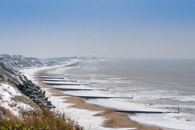 Bournemouth seafront in winter. Southbourne, Bournemouth seafront with groynes looking towards Hengistbury Head in winter, with snow on beach stock images