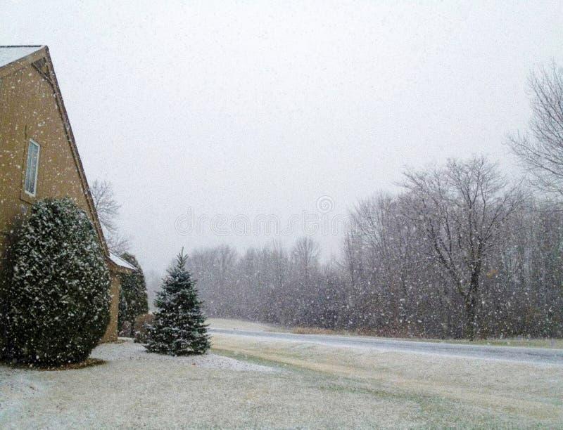 Bourrasques de neige couvrant à la maison, yard, route et arbres nus image stock