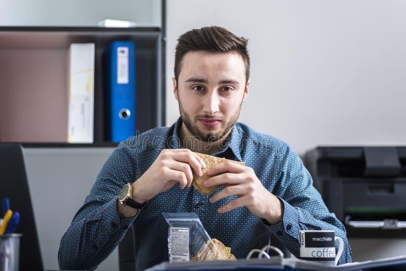 Bourreau de travail mangeant le petit déjeuner tout en travaillant photo libre de droits