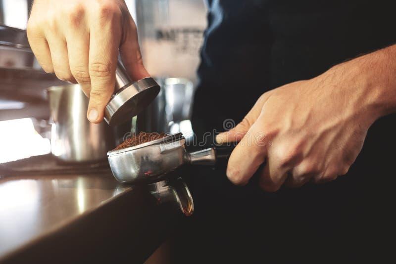 Bourreur de participation de barman dans une main allant presser le cafè moulu dans le support pour composer l'expresso pour le c images stock