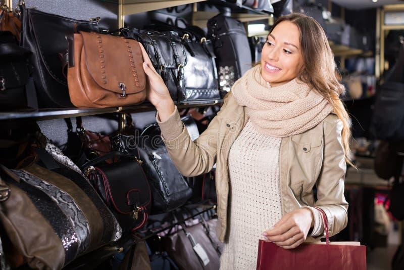 Bourse en cuir de achat de jeune femme dans la boutique photographie stock libre de droits