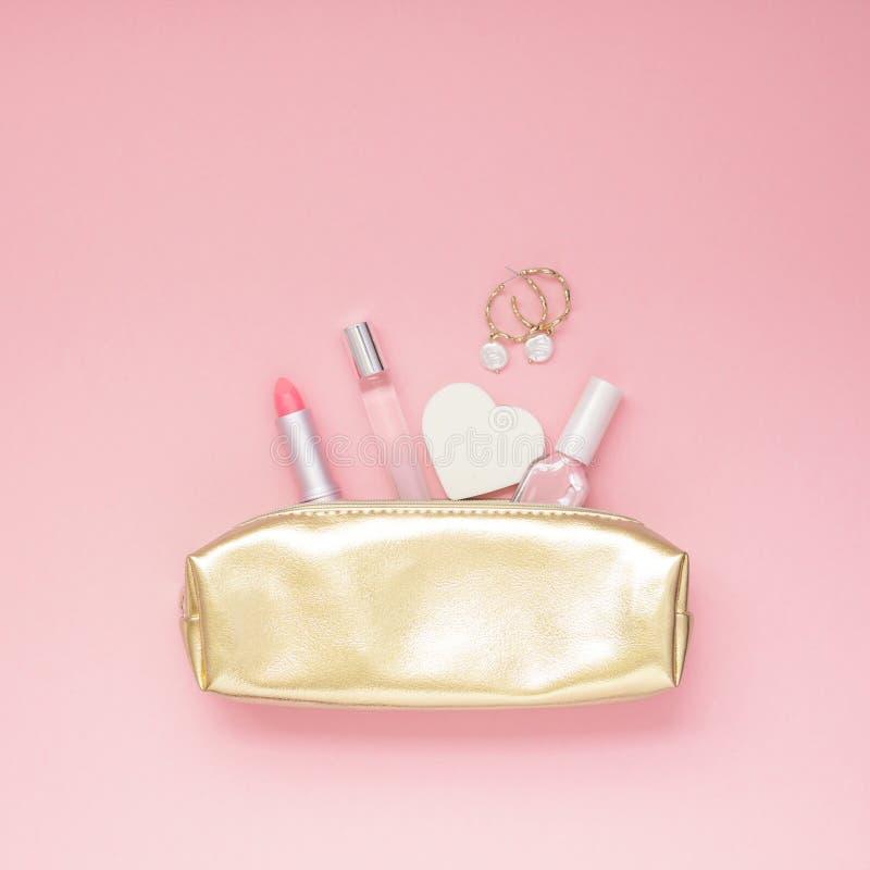 Bourse femelle d'or avec des cosmétiques photographie stock
