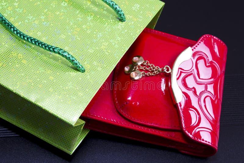 Bourse rouge, sac vert sur le noir photo libre de droits