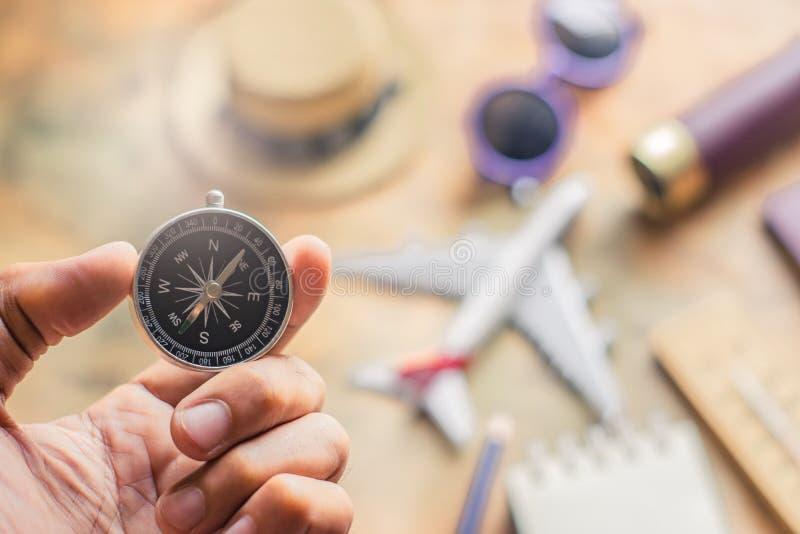 Boussole de participation d'homme sur la note brouillée avec le passeport, jumelles, crayon, avion, fond de carte de papier pour  images stock