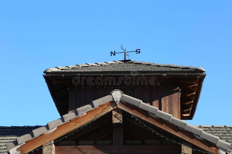 Boussole de toit en métal sur le dessus de toit de bardeau contre le ciel bleu photographie stock libre de droits