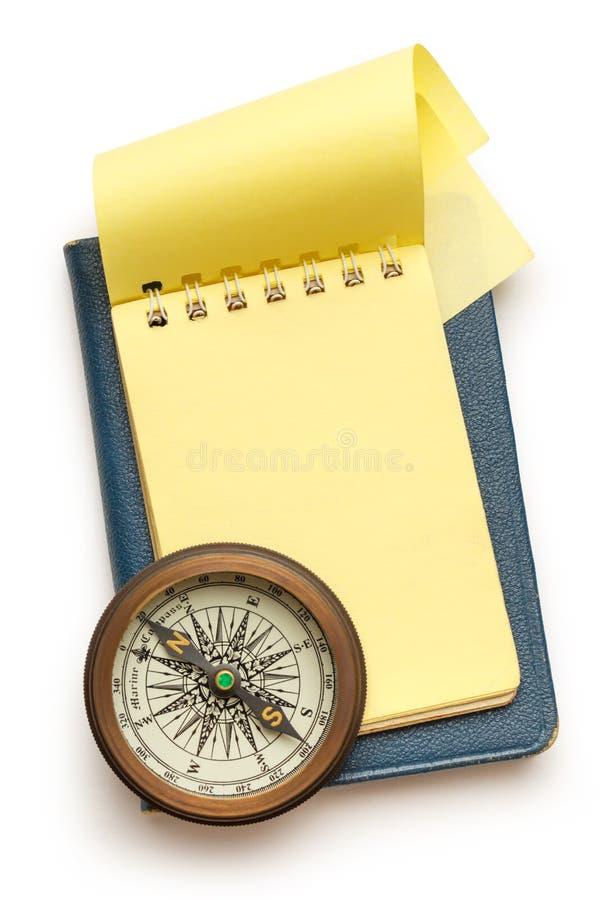 Boussole de vintage et bloc-notes jaune vide photo stock