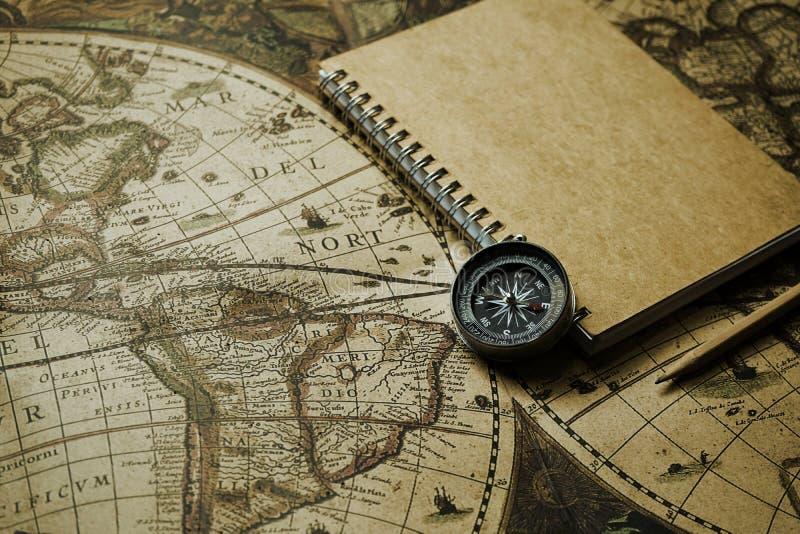 Boussole et carnet sur la carte du monde de vintage de tache floue, concept de voyage, copie photographie stock libre de droits