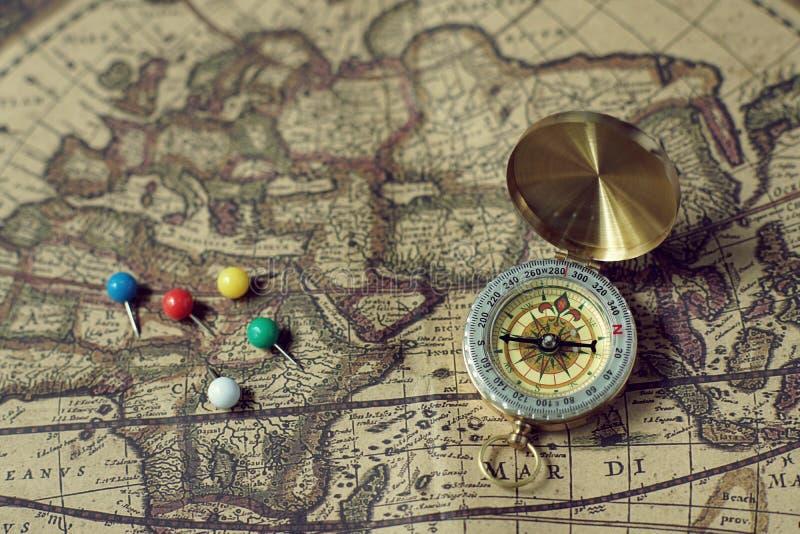 Boussole et goupilles sur la carte du monde de vintage de tache floue, concept de voyage, l'espace de copie photos stock