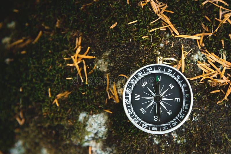 Boussole magnétique avec un cadran noir sur une pierre sauvage couverte de la mousse verte Le concept de trouver la manière et image libre de droits