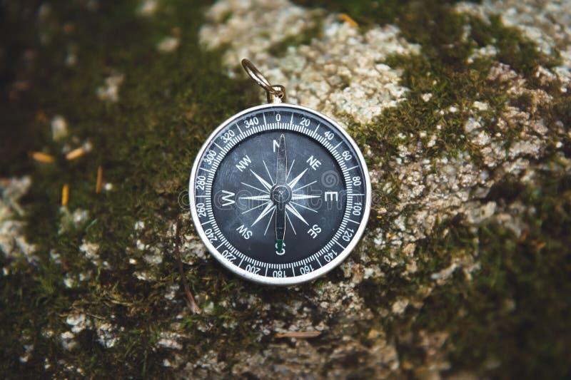 Boussole magnétique avec un cadran noir sur une pierre sauvage couverte de la mousse verte Le concept de trouver la manière et image stock