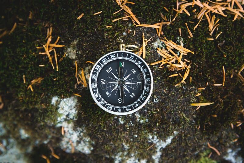 Boussole magnétique avec un cadran noir sur une pierre sauvage couverte de la mousse verte Le concept de trouver la manière et photo stock