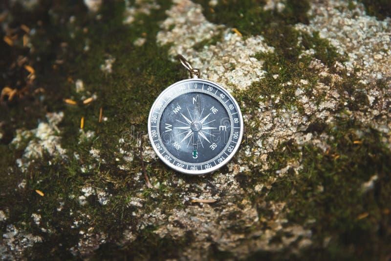 Boussole magnétique avec un cadran noir sur une pierre sauvage couverte de la mousse verte Le concept de trouver la manière et images libres de droits