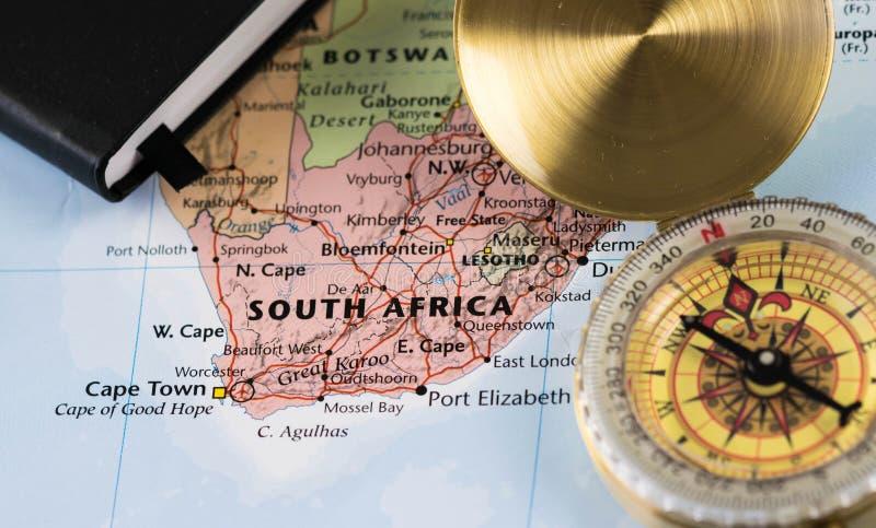 Boussole sur une fin vers le haut de la carte se dirigeant chez l'Afrique du Sud et prévoyant une destination de voyage photographie stock