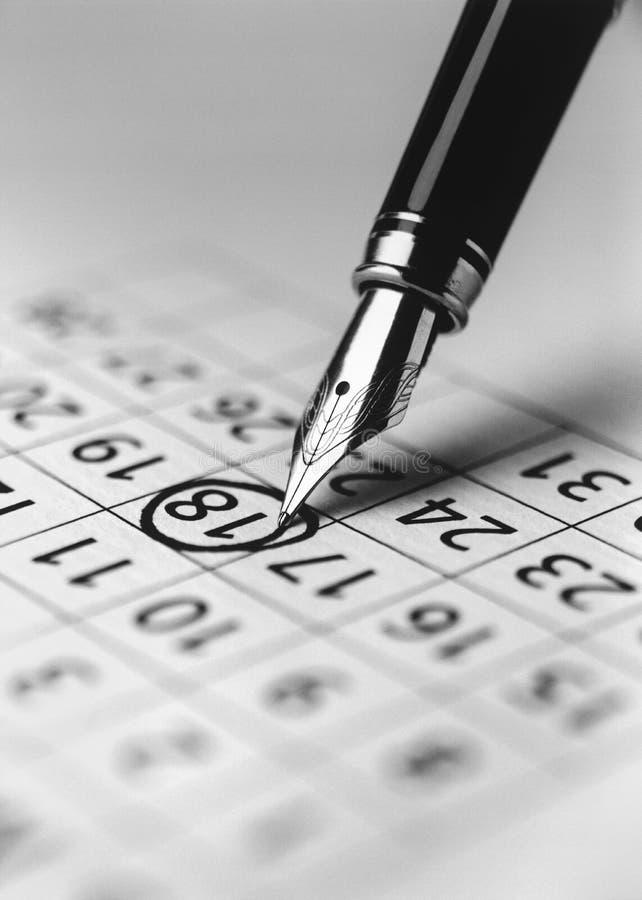 Bout de date d'inscription de stylo-plume dans le calendrier (b&w) (plan rapproché) image libre de droits