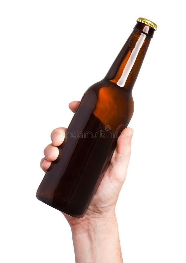 Bouteille à bière de Brown à disposition d'isolement sur le fond blanc photo stock