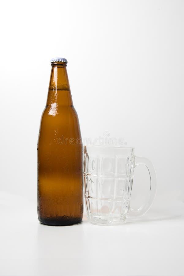 Bouteille à bière de Brown avec le verre de bière vide images stock