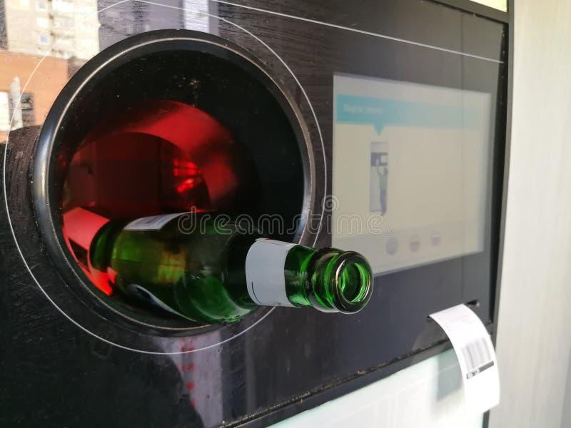 Bouteille à bière insérée dans le distributeur automatique inverse automatique pour la réutilisation photo libre de droits