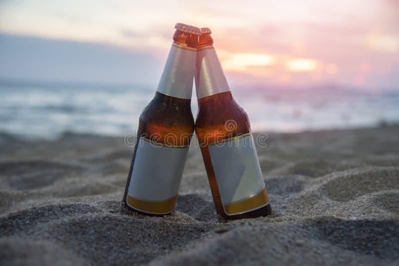 Bouteille à bière sur la plage sablonneuse avec le fond de mer d'océan de coucher du soleil pour la partie de plage image libre de droits