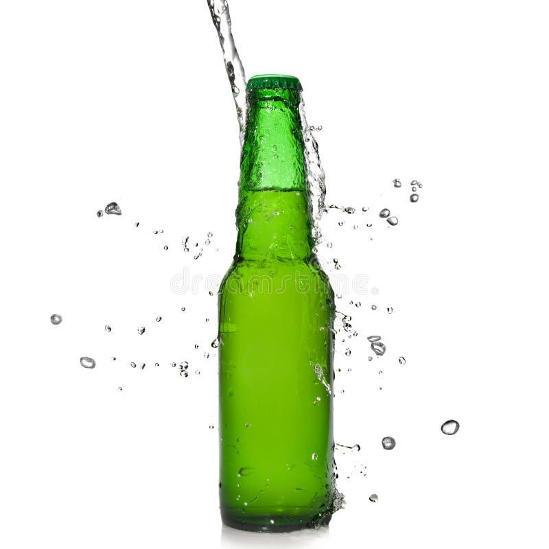 Bouteille à bière verte avec l'éclaboussure de l'eau photographie stock libre de droits