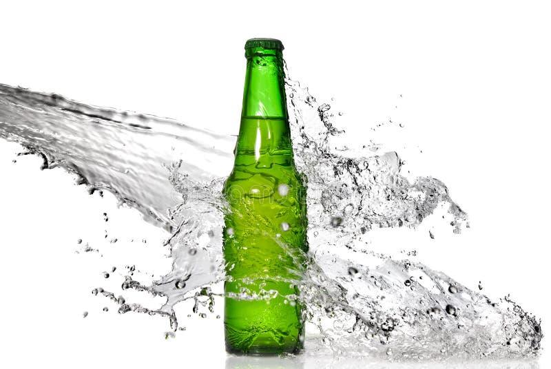 Bouteille à bière verte avec l'éclaboussure de l'eau images libres de droits