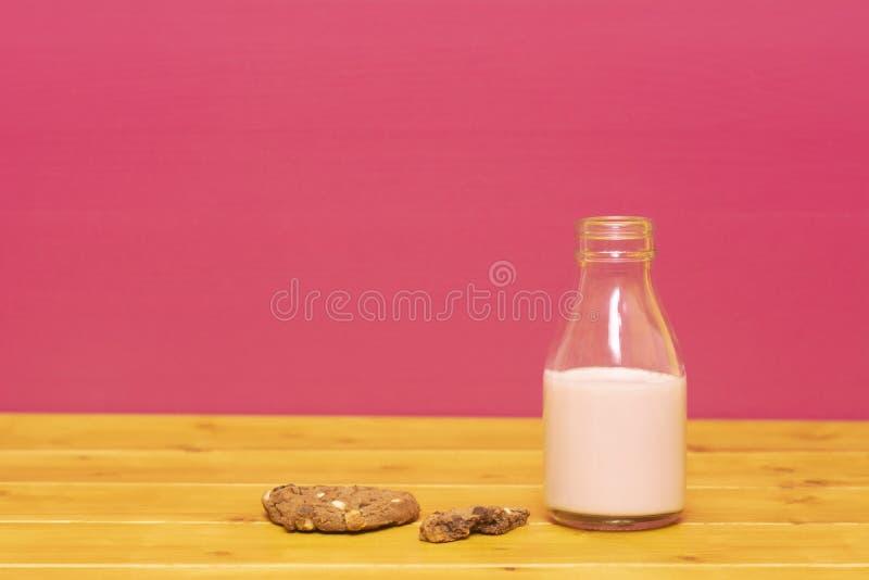 Bouteille à lait à moitié pleine du milkshake de fraise avec le biscuit à moitié mangé image stock