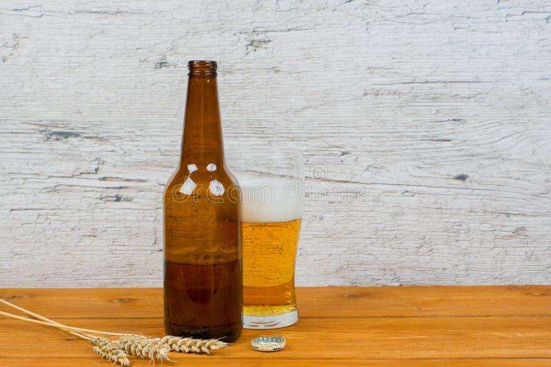 Bouteille à moitié vide de bière et plein verre photos libres de droits