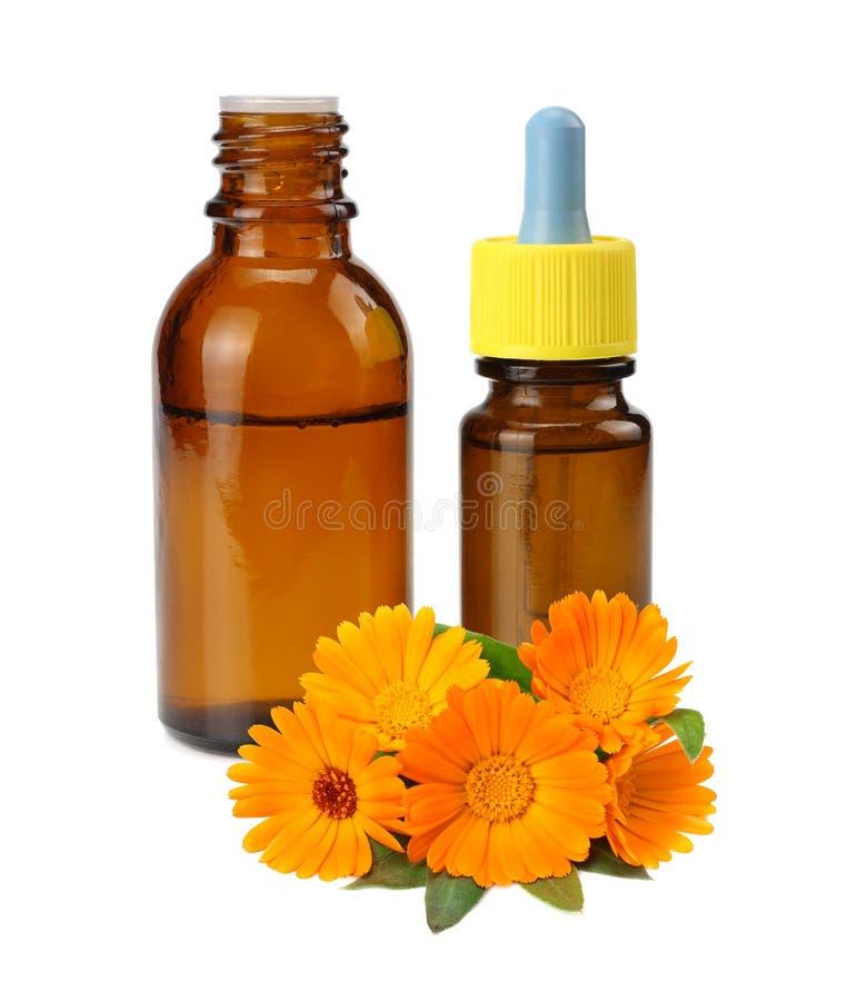 bouteille avec de l'huile de souci avec des fleurs de souci d'isolement sur le fond blanc Fleur de Calendula photo libre de droits